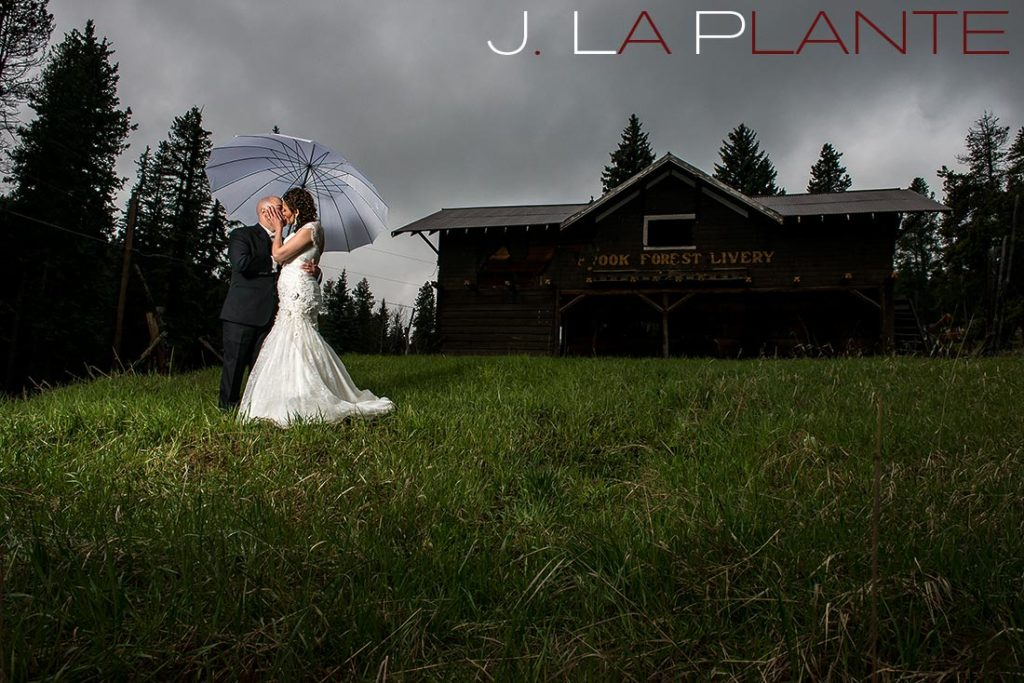 J. La Plante Photo | Brook Forest Inn Wedding | Evergreen, CO wedding photography | Bride and groom under umbrella in rainy field
