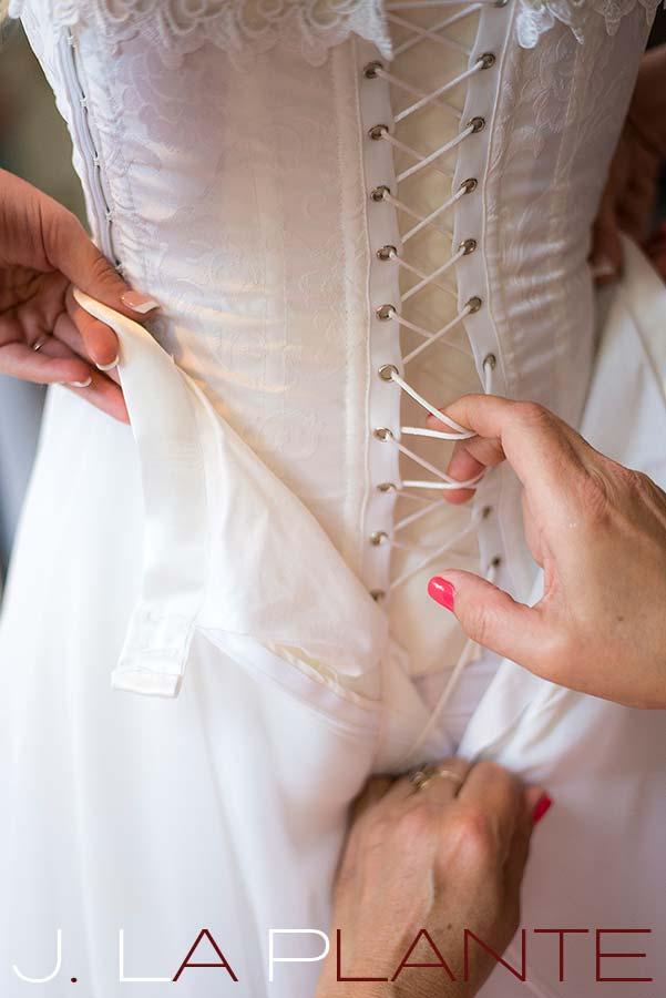 J. La Plante Photo | Destination Wedding Photography | Ogunquit Maine Wedding | Wedding gown corset being laced up