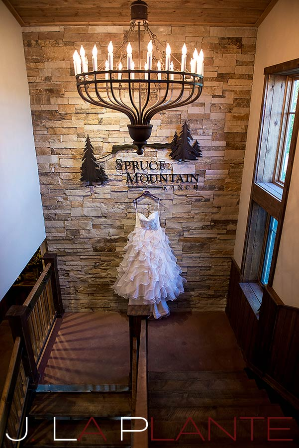 J. La Plante Photo | Colorado Wedding Photography | Spruce Mountain Ranch Wedding | Wedding gown hanging under chandelier