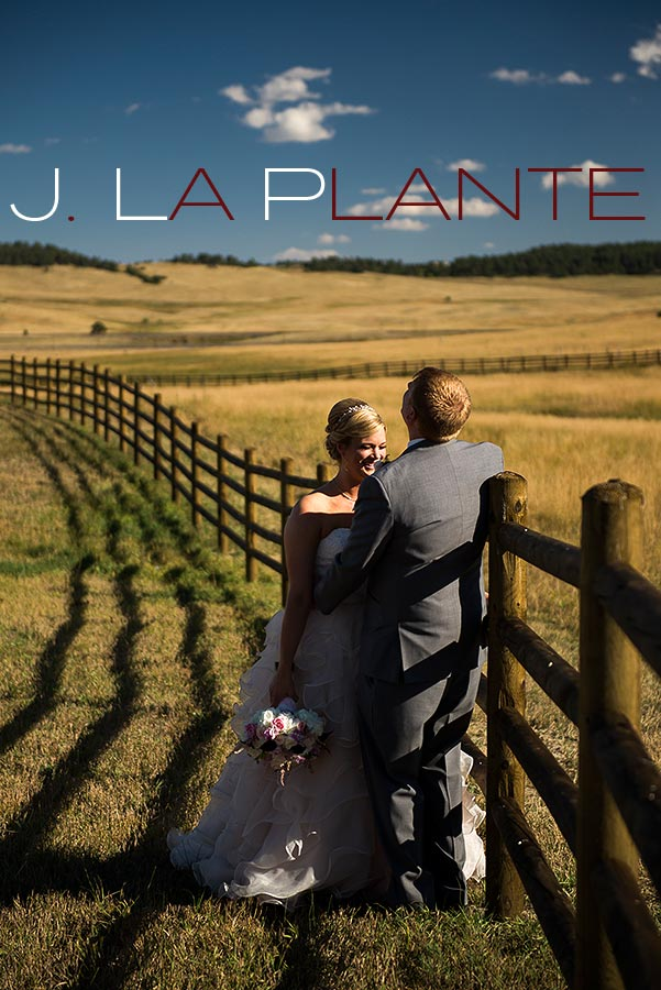 J. La Plante Photo | Colorado Wedding Photography | Spruce Mountain Ranch Wedding | Bride and groom laughing by fence