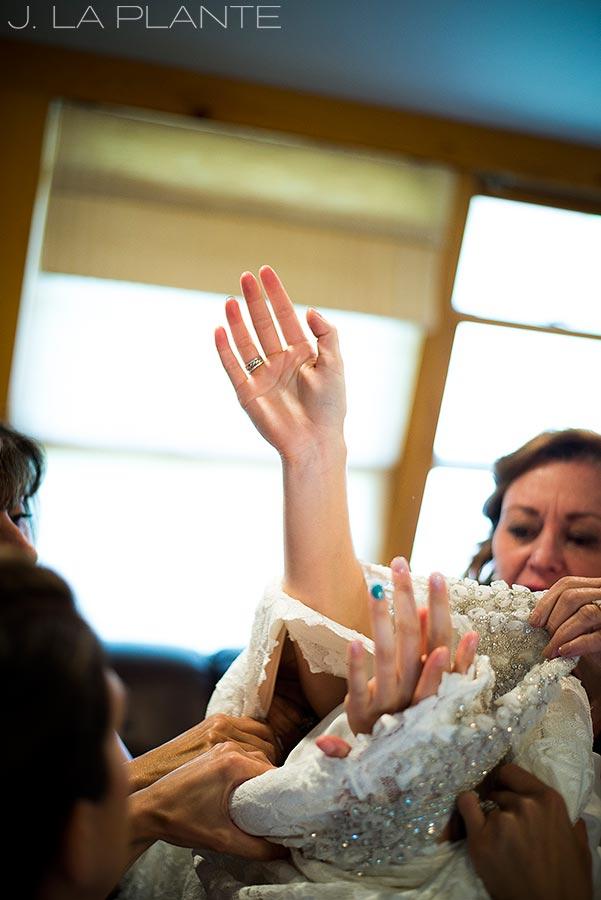 J. La Plante Photo | Boulder Wedding Photographer | Planet Bluegrass Wedding | Bride Struggling Into Dress