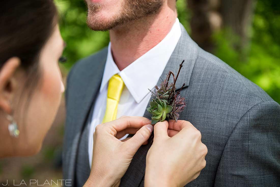 J. La Plante Photo | Boulder Wedding Photographer | Planet Bluegrass Wedding | Bride Pinning Boutonniere on Groom