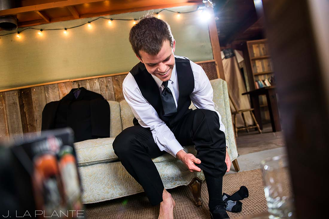 J. LaPlante Photo | Boulder Wedding Photographers | River Bend Wedding | Groom Putting on Socks