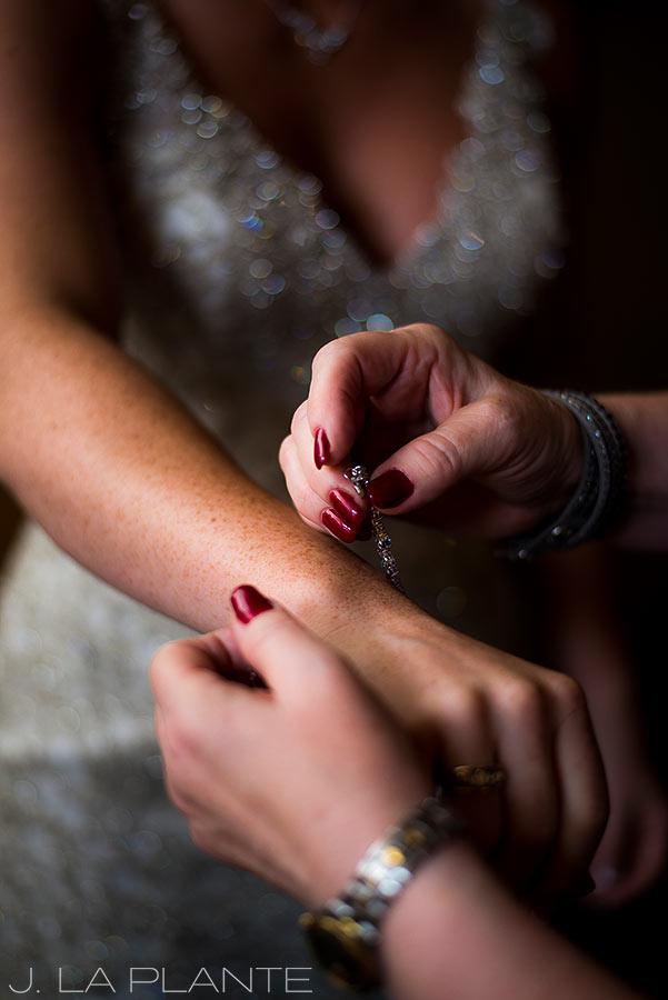 J. La Plante Photo | Winter Park Colorado Wedding Photographer | Devil's Thumb Ranch Wedding | Bride Putting on Bracelet