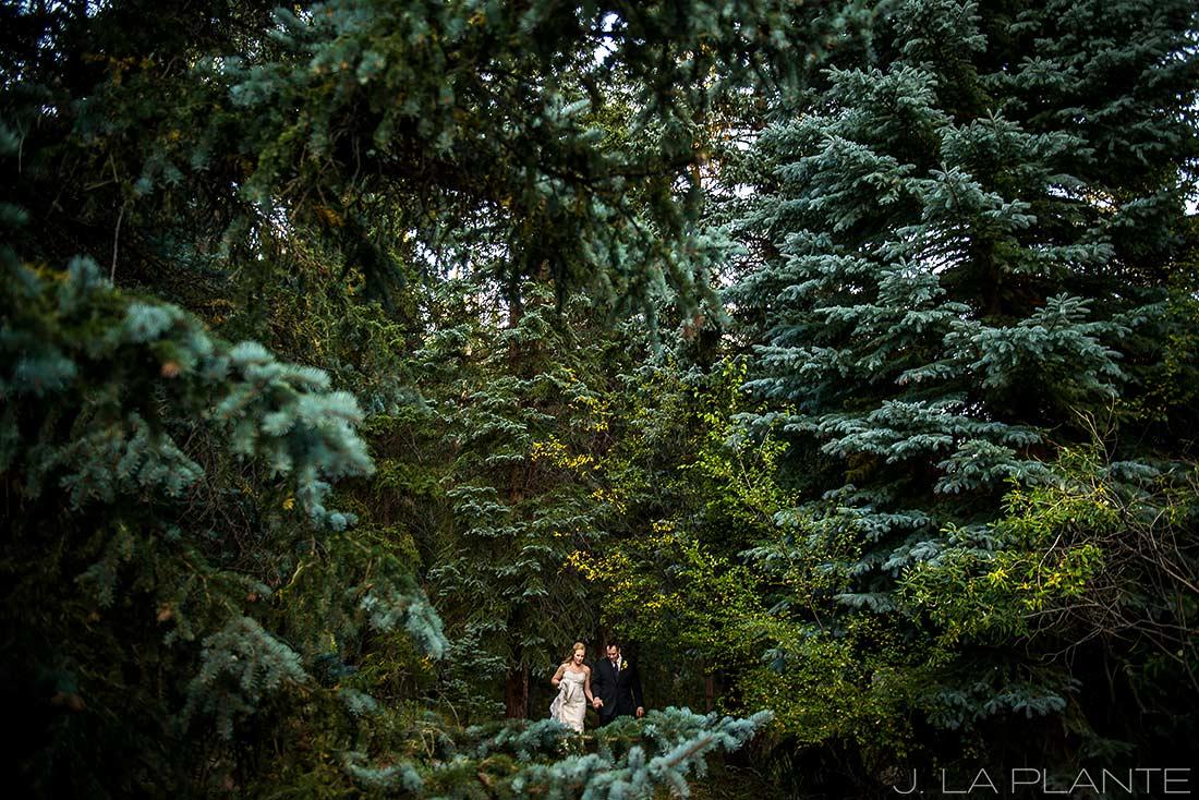 J. LaPlante Photo | Colorado Wedding Photographers | Lower Lake Ranch Wedding | Bride and Groom Walking Through Woods
