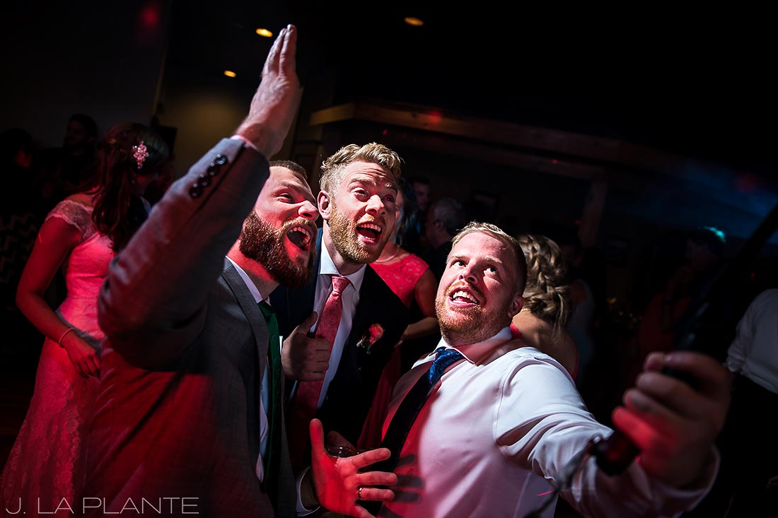 groom using selfie stick with guests during reception