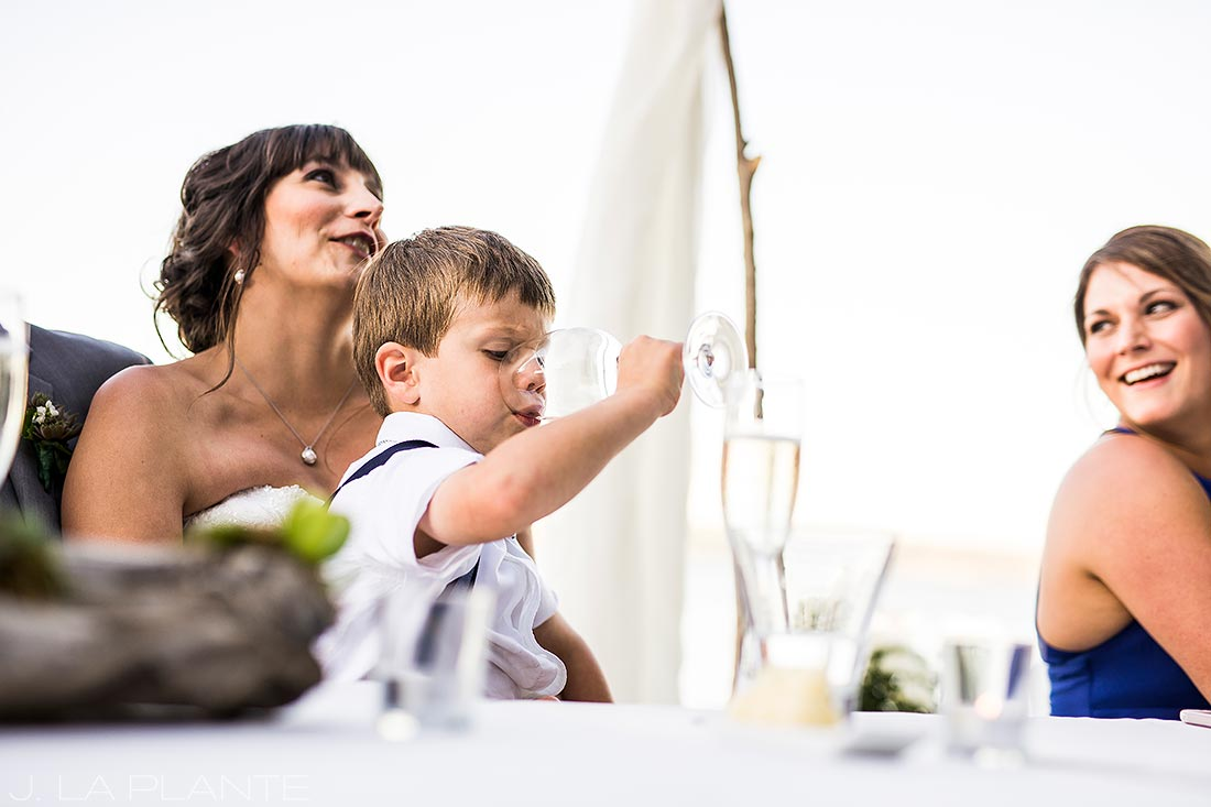 ring bearer sneaking champagne during toasts