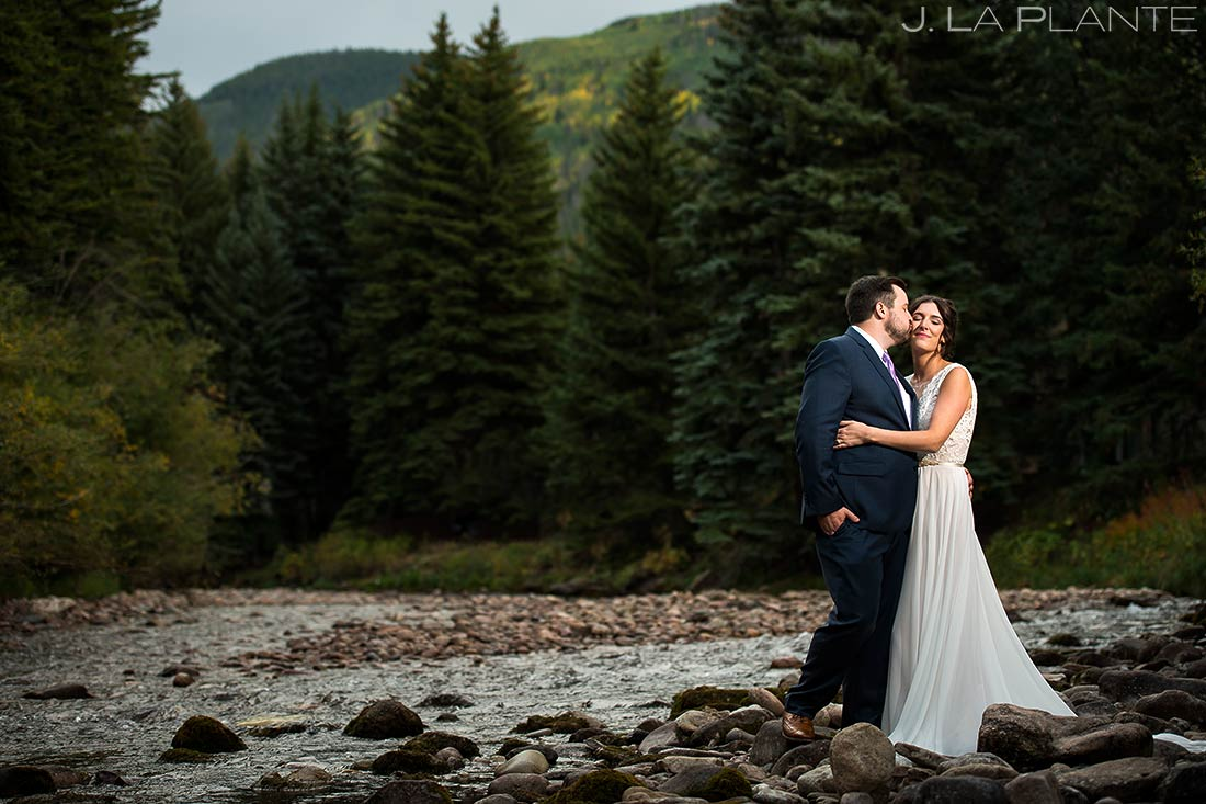 Bride and Groom Kissing by River | Sonnenalp Hotel Wedding | Vail Wedding Photographer | J. La Plante Photo