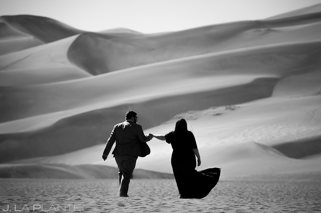 bride and groom hiking the great sand dunes