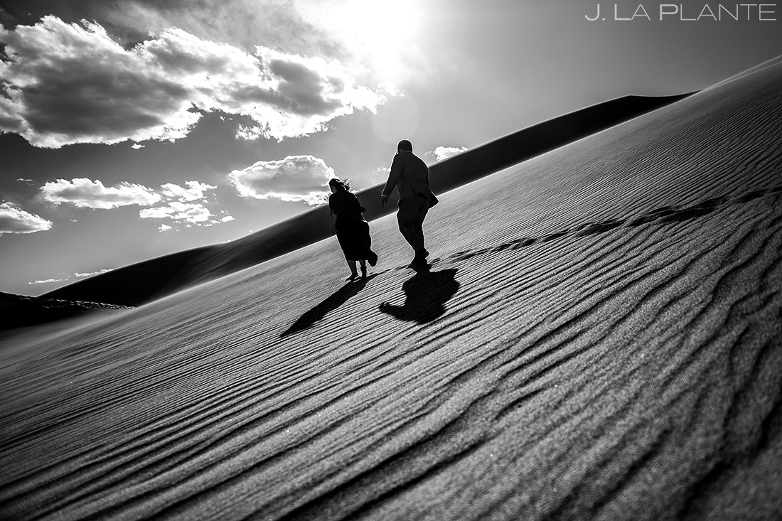 bride and groom hiking the sand dunes