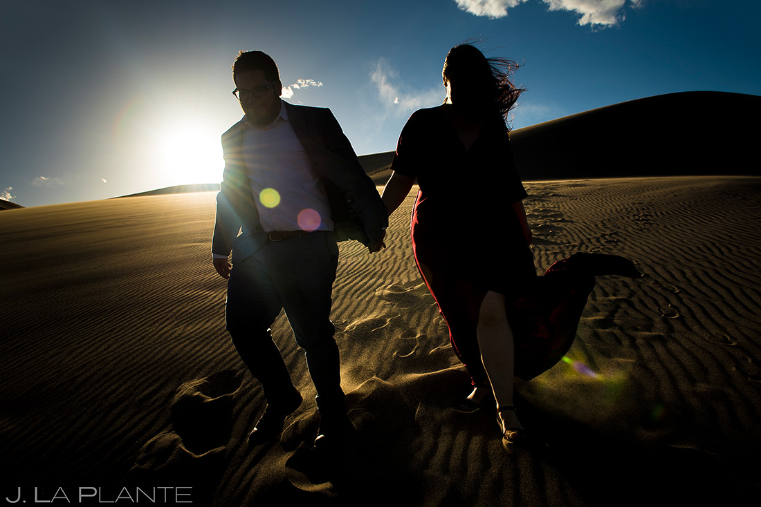 bride and groom hiking the great sand dunes at sunset