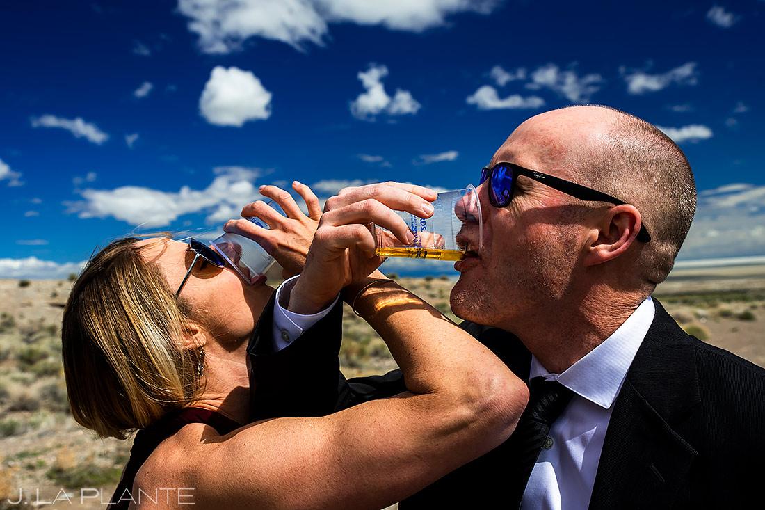 Bride and Groom Doing Shots | Bonneville Salt Flats Engagement | Destination Wedding Photographer | J. La Plante Photo