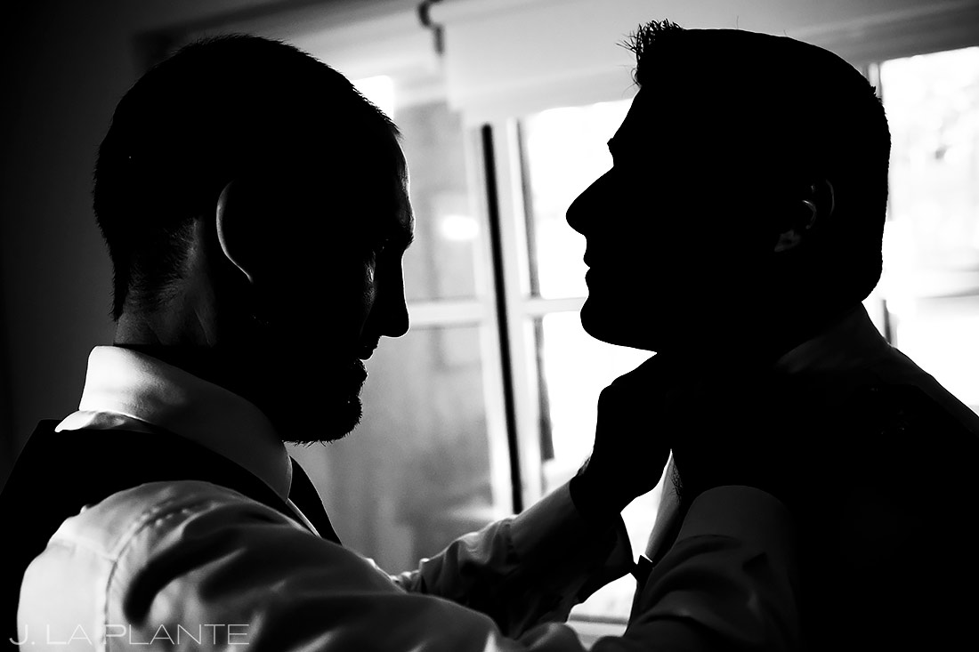 groom getting ready groomsman tying tie