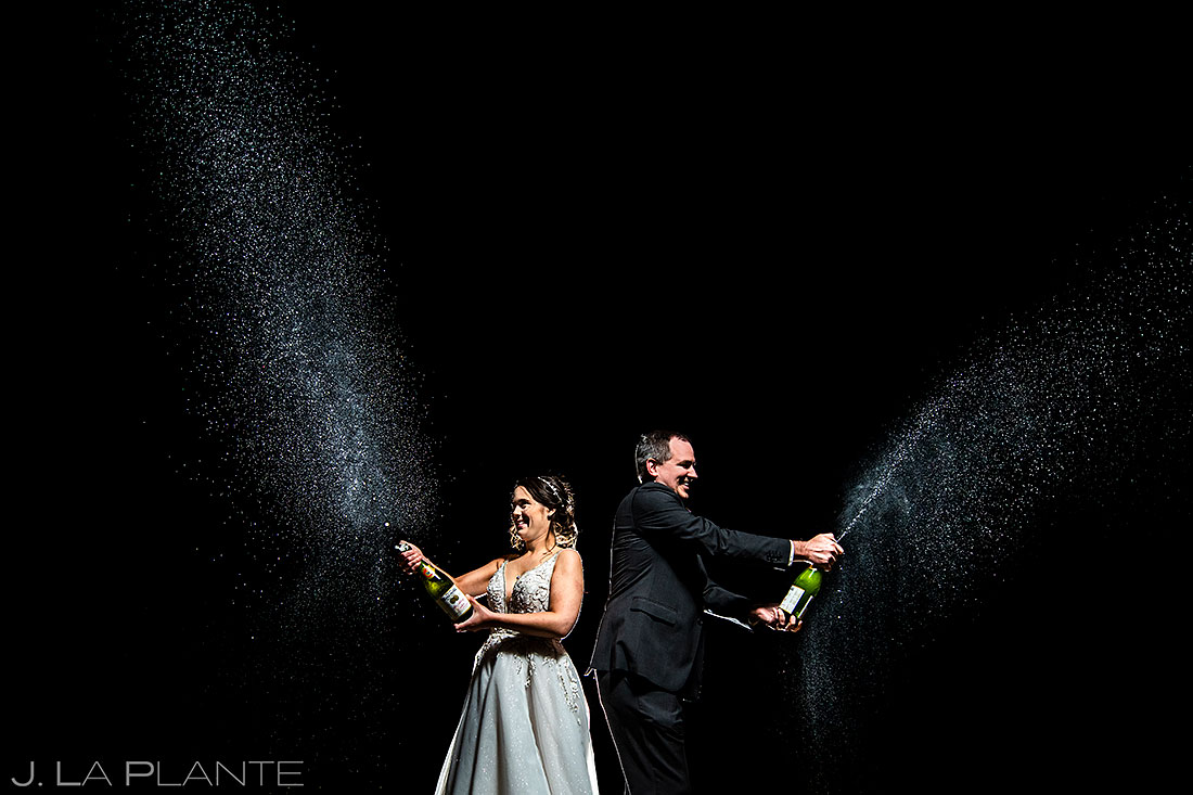 bride and groom spraying champagne in colorado
