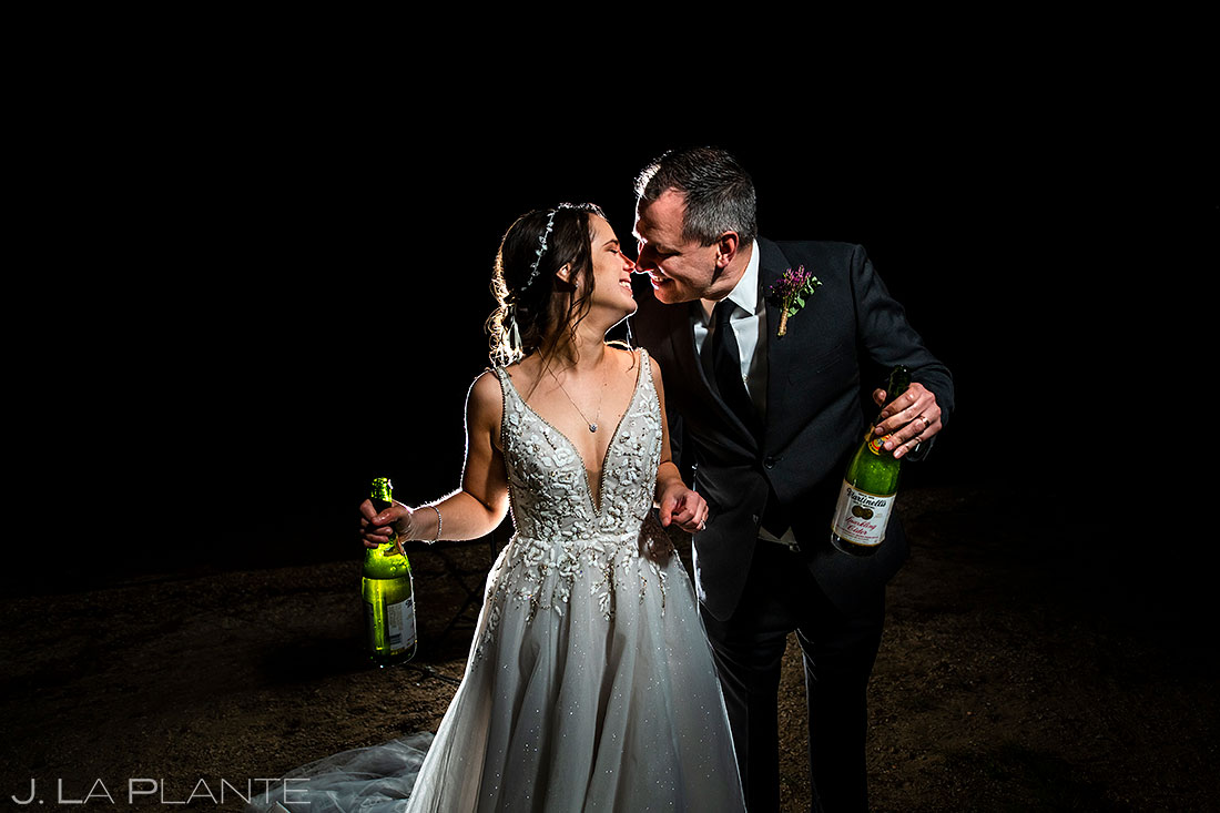 nighttime wedding photo bride and groom drinking champagne