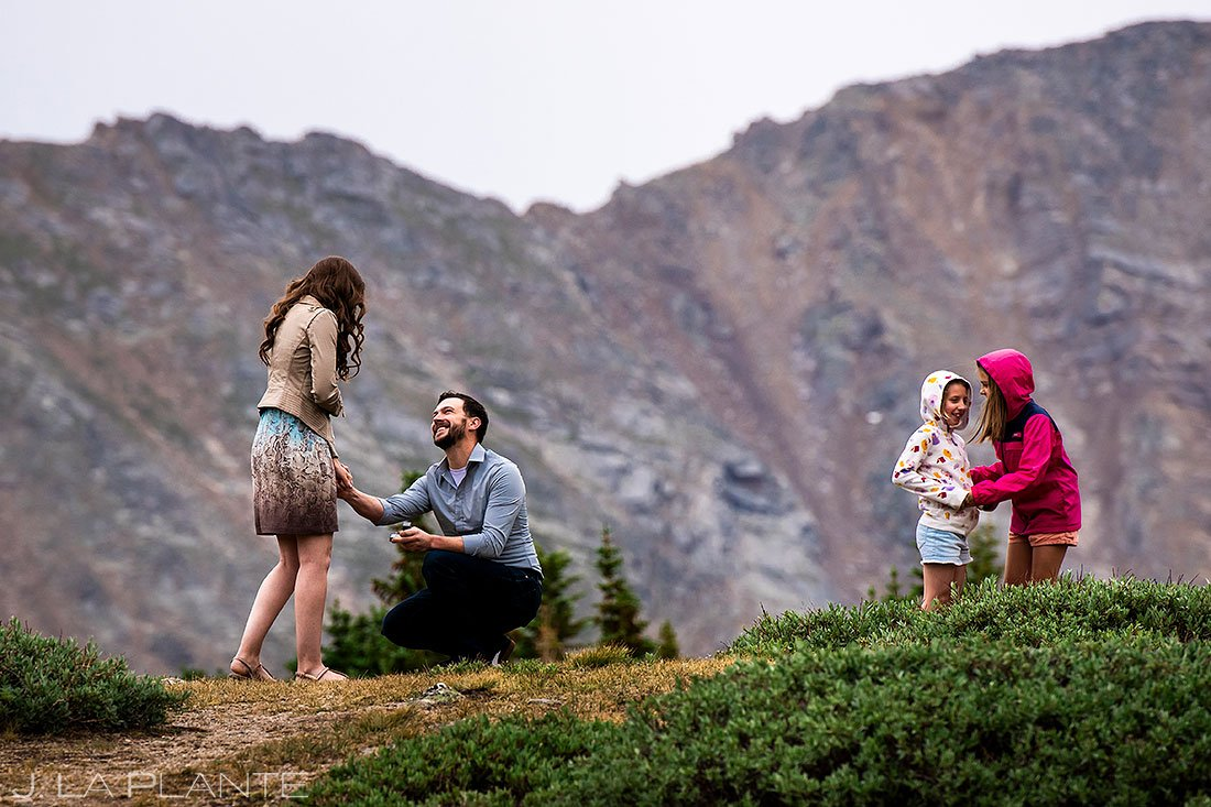 guy proposing to girlfriend on top of loveland pass engagement session