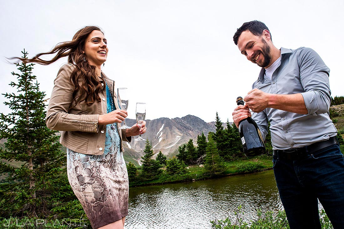 bride and groom drinking champagne during loveland pass engagement session