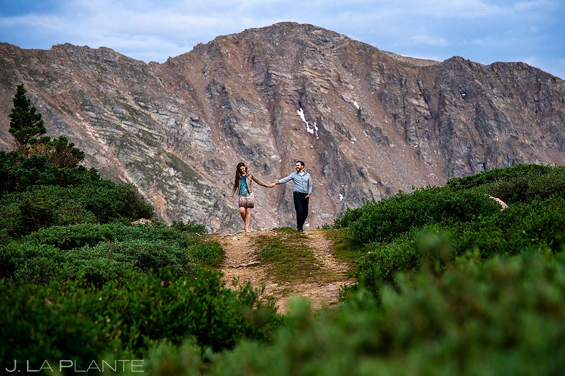 bride and groom to be hiking in the rocky mountains