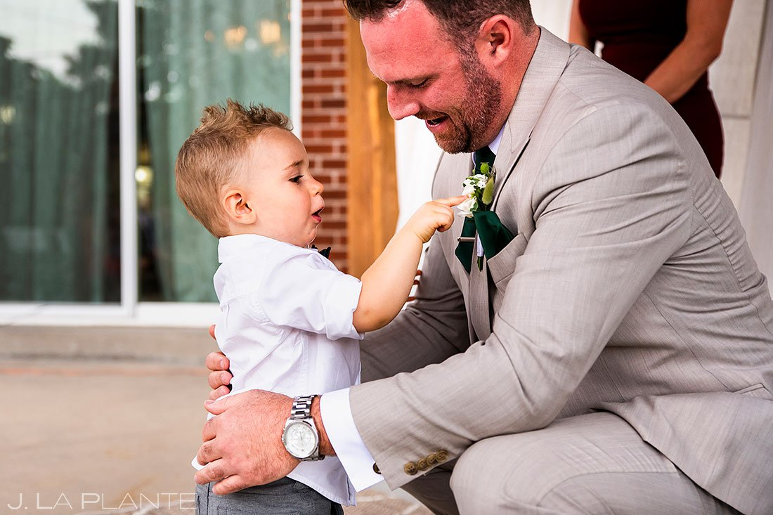 cute ring bearer playing with groom's boutonniere