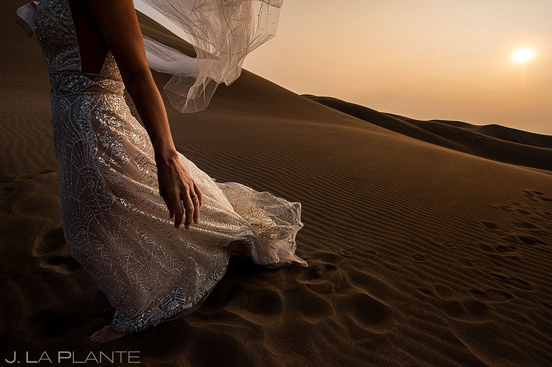 unique detail photo of bride's wedding dress and veil at sunset