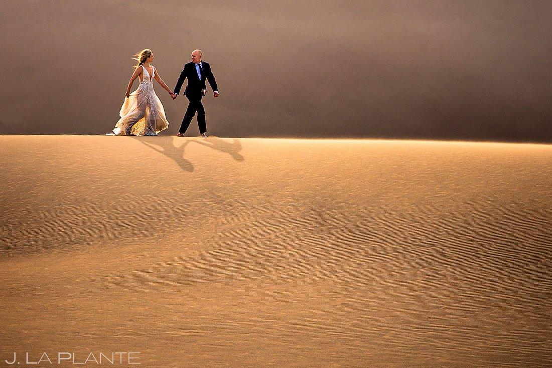 bride and groom walking along sand dunes