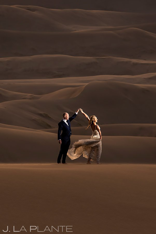 bride and groom dancing on sand dunes