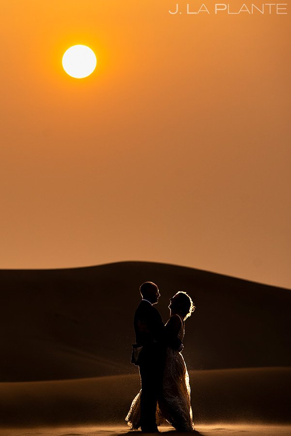 silhouette wedding photo of bride and groom at sunset