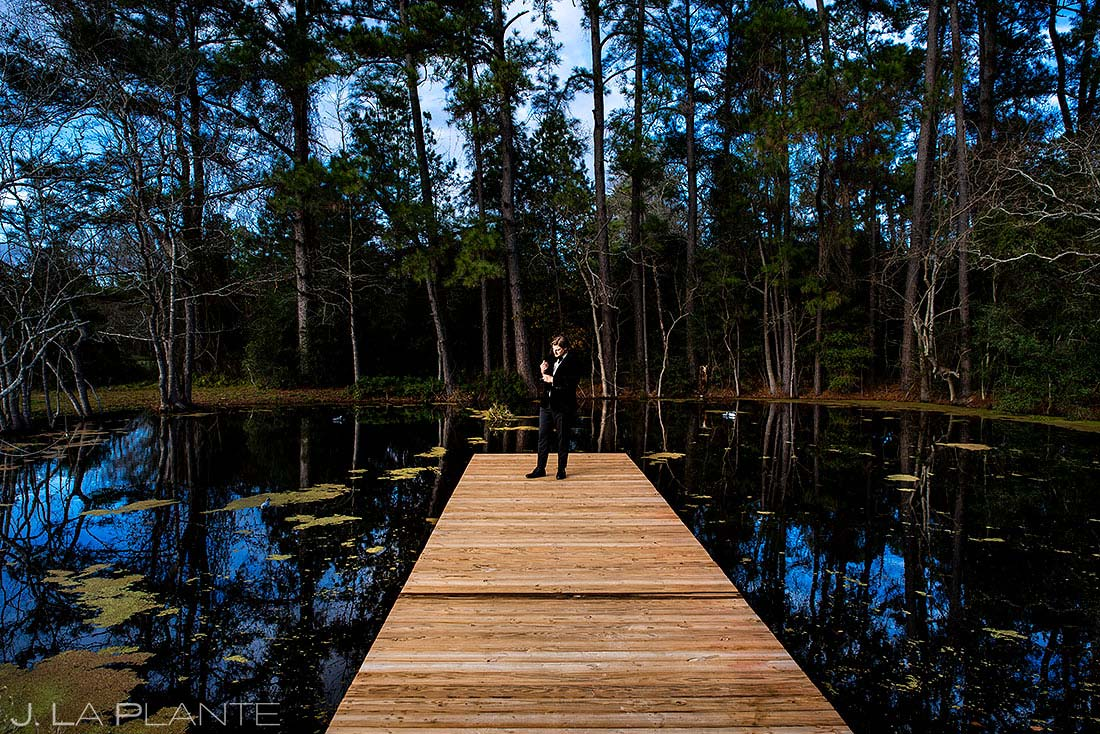 unique portrait of groom standing on a dock